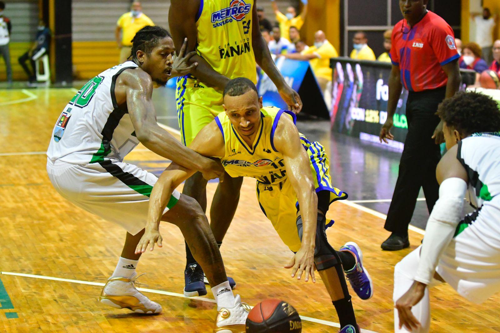 Adrís De León, de Metros, driblea entre los jugadors de Soles, Malik Pope y Kelvin Peña.