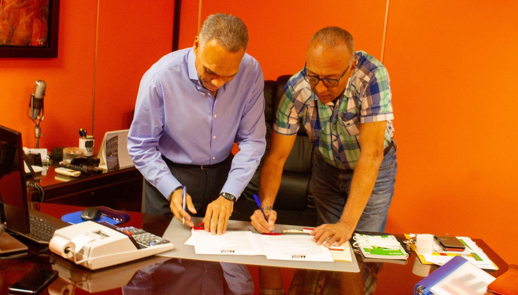 Danny Pérez, director de Neón 89.3 FM y Raphy D'Oleo, firman el contrato de el Navican de Neón..